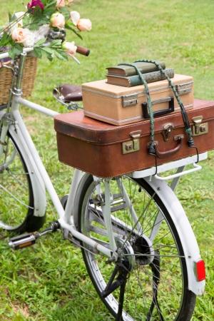 Vintage fiets op het veld met een mand met bloemen en tas Stockfoto