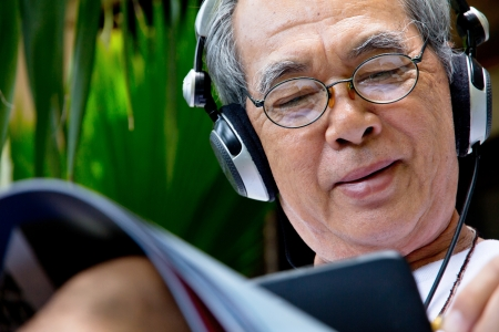 asian man: Senior man enjoying music on his tablet