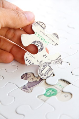 seeking solution: hand holding a puzzle piece, Finance concept