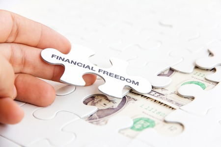financial freedom: hand holding a puzzle piece, financial freedom concept