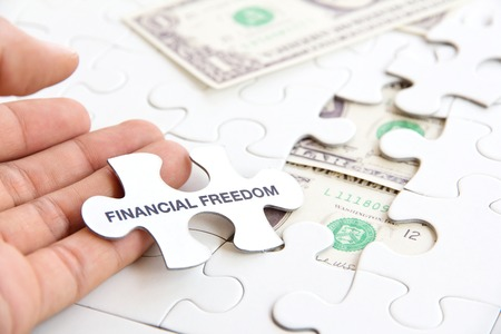 hand holding a puzzle piece, financial freedom concept