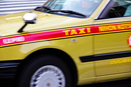 yellow taxi: Yellow taxi speeding around the corner in the streets of Tokyo, Japan  Motion Blur Stock Photo
