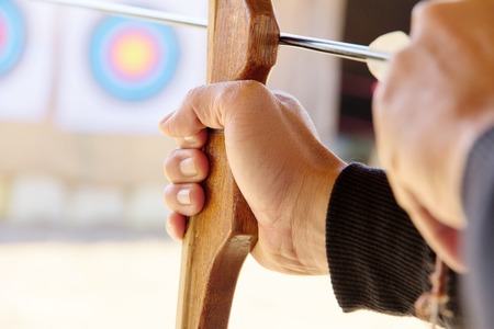 medalist: Archer holds his bow aiming at a target Stock Photo