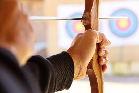 shooting: Archer sostiene su arco apuntar a un blanco