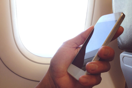 cell: business man sits in airplane watching his cell phone