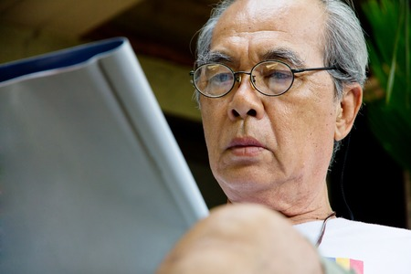 southeast asian ethnicity: Senior man relaxing at home reading a book Stock Photo