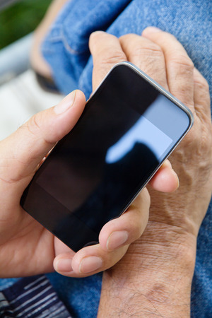 wireless telephone: Close up of older man hand holding a smart phone