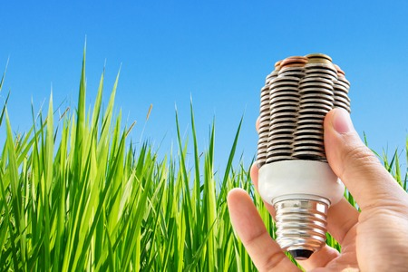 creativity symbol: hand holding coin light bulb,energy concept