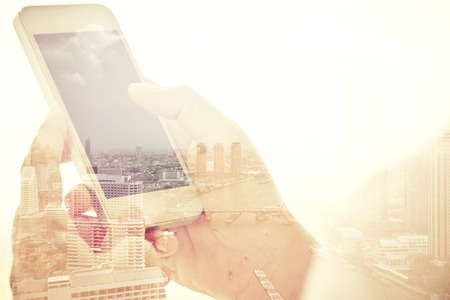 business concepts: Using smart phone double exposure and cityscape background. Business  technology concept.