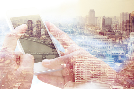 finance concept: Using smart phone double exposure and bangkok cityscape in the background