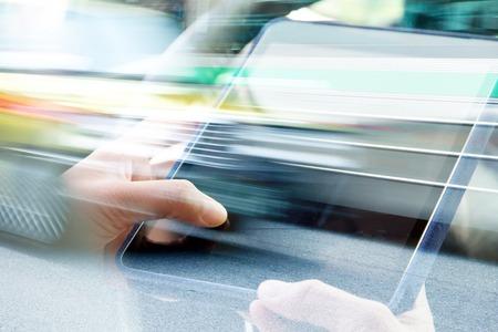 comunicação: Usando a exposição tabuleta digital de casal e vista borrada de carro na rua da cidade Banco de Imagens