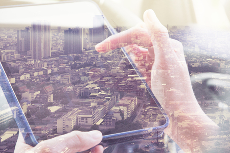 テクノロジー: デジタル タブレットの二重露光を使用してと、都市景観の背景。ビジネス技術コンセプト。