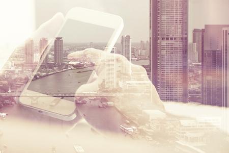 스마트 폰과 도시 배경, 비즈니스 기술 개념을 가진 사람들의 이중 노출 이미지.