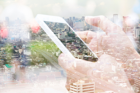 technology: Double exposure image of people with smart phone and cityscape background,Business technology concept.