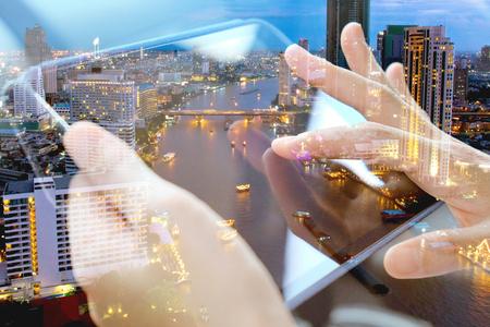 El uso de la tableta digital y doble exposición y el fondo del paisaje urbano. Concepto de tecnología de negocios.