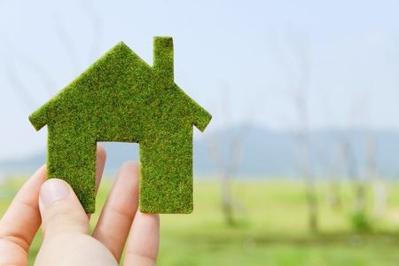 creativity symbol: hand holding eco house icon concept