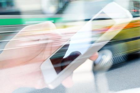 communication: Utilisation de téléphone intelligent double exposition et vue floue de voiture sur rue de la ville Banque d'images