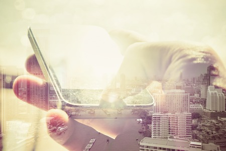 wireless technology: Double exposure image of people with smart phone and cityscape background,Business technology concept.