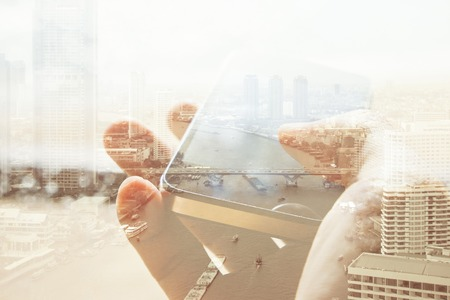 digital composite: Double exposure of cityscape and smart phone, business technology concept.