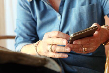 manos sosteniendo: image of older woman using smart phone