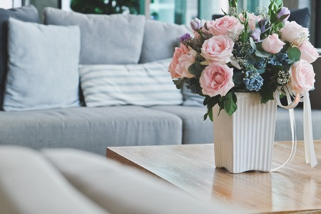 living room: Beautiful Pink rose in vase on table in living room. Stock Photo