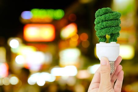 natural phenomenon: hand holding green light bulb and defocused city night light background, eco energy concept