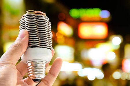 flare stack: hand holding coin light bulb with defocused city night light background, energy concept