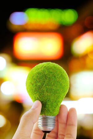green light bulb: hand holding green light bulb and defocused city night light background, eco energy concept