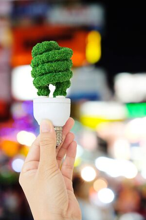 flare stack: green light bulb and defocused city night light background, eco energy concept Stock Photo
