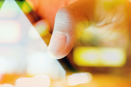 wifi: close up of Male fingers touching tablet screen double exposure and defocused city night light background.