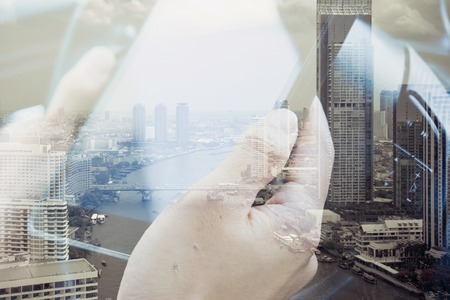 city people: concept image of Business  technology, Using digital tablet double exposure and and cityscape background.