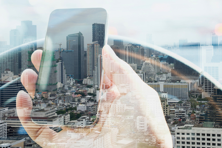digitally: Double exposure of man using smart phone and cityscape background,  urban lifestyle and communication technology concept.