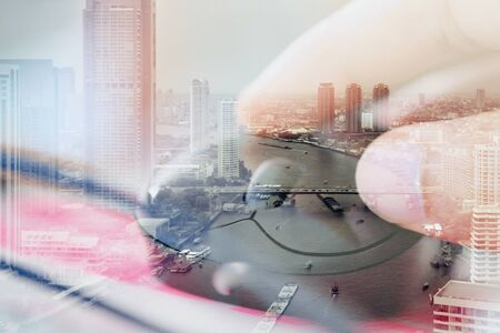 computer peripheral: Double exposure image of woman hand on computer mouse and cityscape background,communication technology concept.
