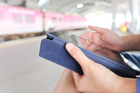 palmtop: Social Media Life,close up image of business women Sitting in the Skytrain station and Using digital tablet. Stock Photo