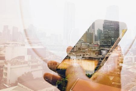 exposicion: Doble exposición de la imagen de hombre de negocios sentado en el avión y el uso de los teléfonos inteligentes con el fondo del paisaje urbano, el concepto de tecnología de negocios.