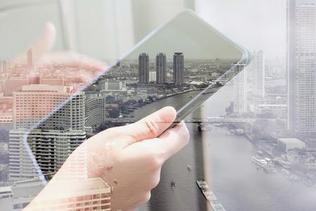 通信: デジタル タブレットの二重露光を使用してと、都市景観の背景。ビジネス技術コンセプト。