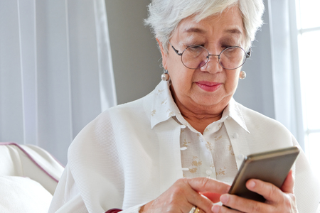 using phone: Senior woman using her mobile phone.