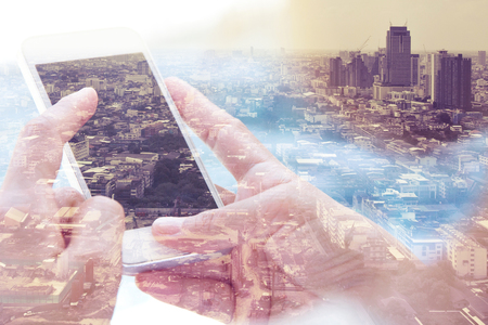 composite image: Double exposure image of smart phone with cityscape background,Communication technology concept Stock Photo