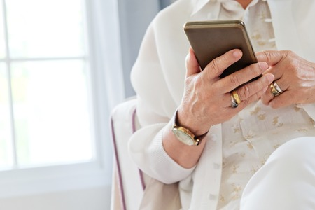 device: Senior woman using her mobile phone.