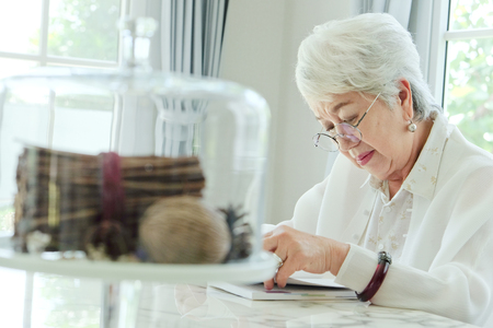 one senior woman only: Senior woman reading a book at home