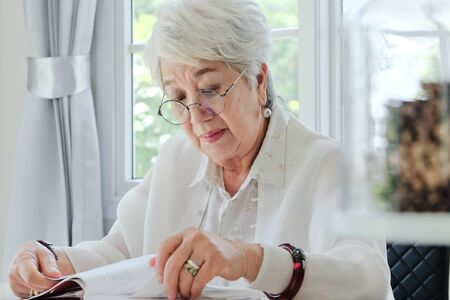 only senior women: Senior woman reading a book at home
