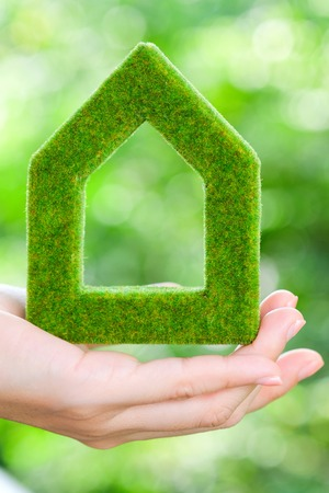 home and garden: hand holding green house icon concept