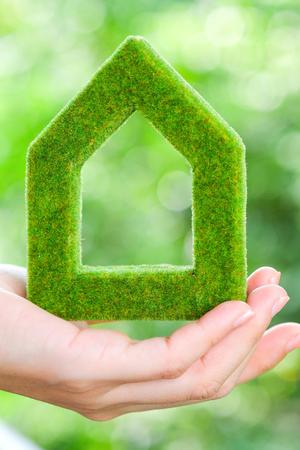 sostiene icono de la casa verde concepto de mano