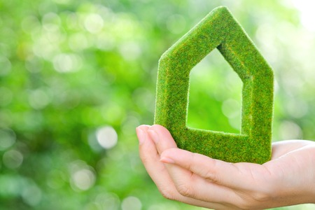 eco house: hand holding green house icon concept