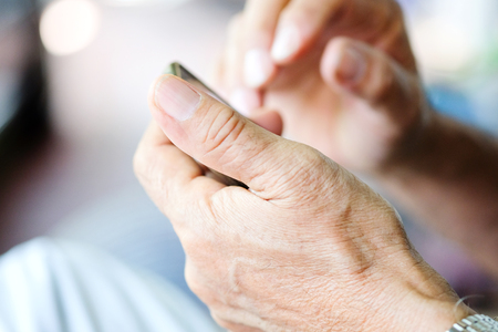 wireless telephone: Close up of older man checking his phone background