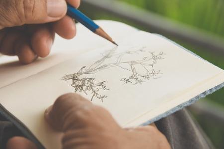 persona escribiendo: hombre que escribe un árbol en bloc de dibujo, concepto conservador de Medio Ambiente Foto de archivo