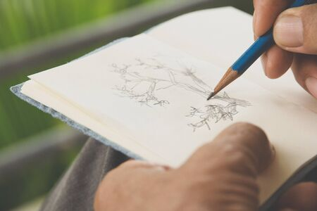 person writing: man writing a tree on sketchbook,Environment Conservative concept
