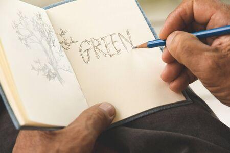 hombre escribiendo: hombre que escribe un árbol en bloc de dibujo, concepto conservador de Medio Ambiente Foto de archivo