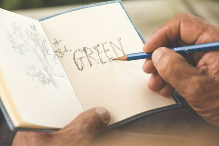 hand writing: man writing a tree on sketchbook,Environment Conservative concept