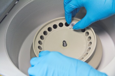 realtime: Research scientist putting test tube into real-time pcr machine close up